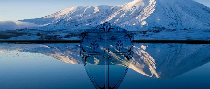 A shield with a cross in it. Overlayed a sheild onto a Mountain Smow covered mountain and lake